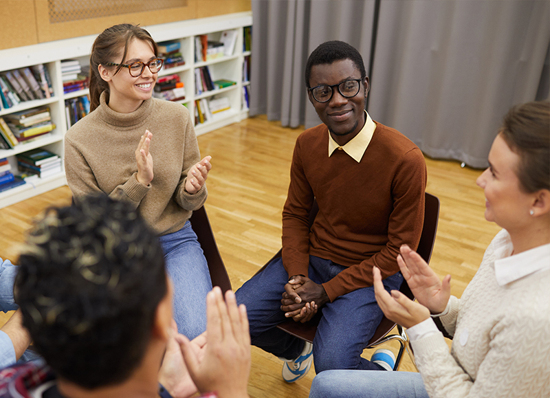 Support Group with multiple young adults sitting in chairs talking with each other