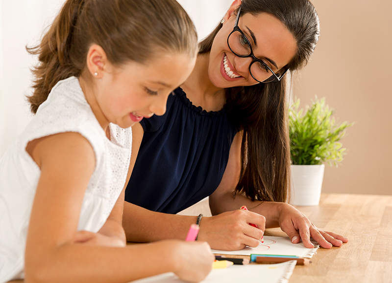 Mother smiling while helping daughter with homework